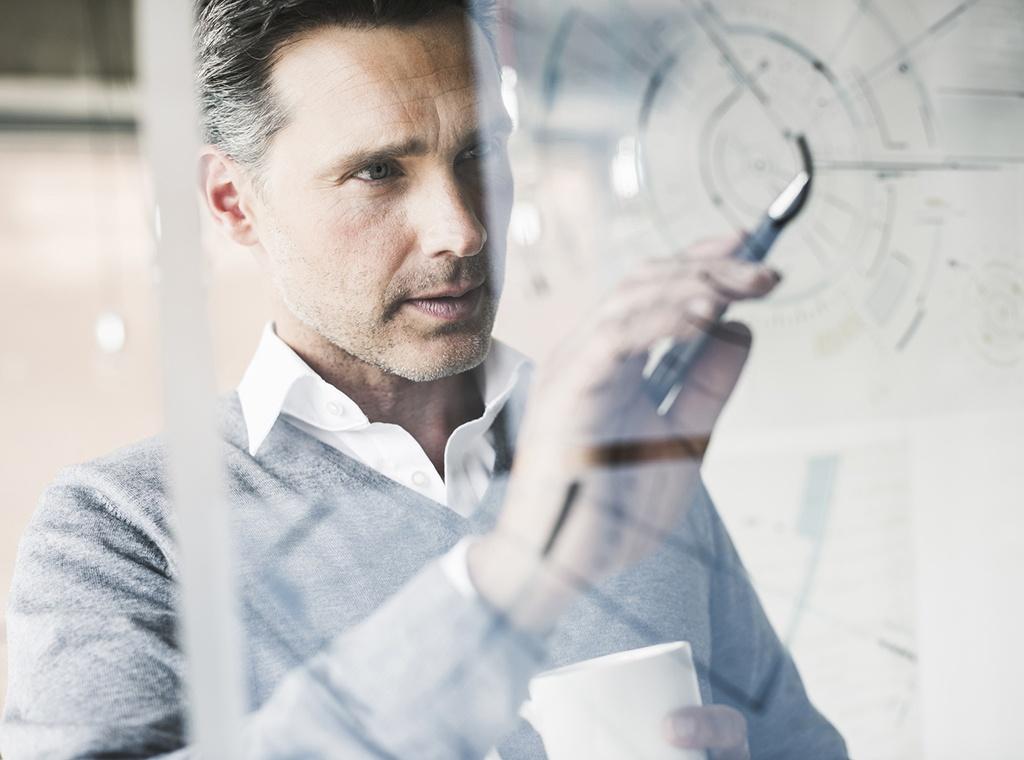 Man sketching plans on a glass pane