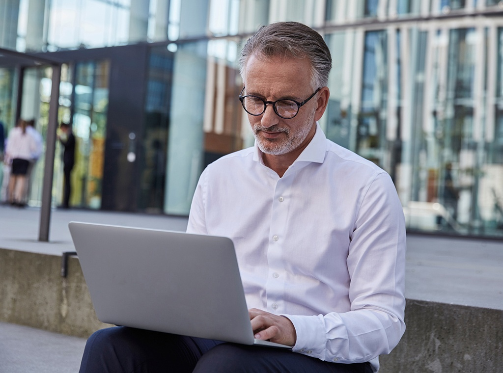 man sitting outside with laptop