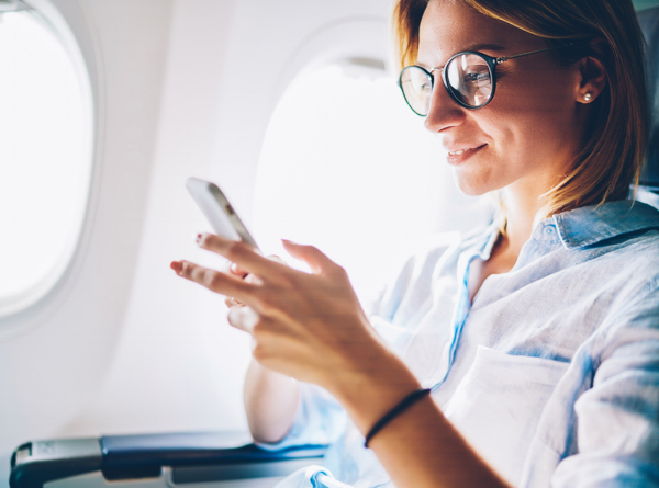 professional female at ease working on her phone while on a plane-754234-edited
